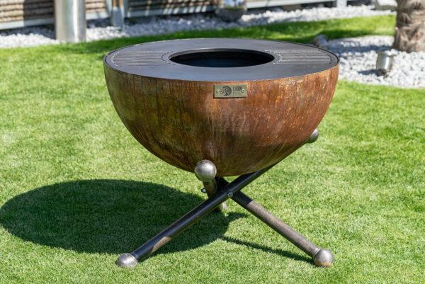 Feuerschale Orbis 100 altum mit Grillring aus Schweizer Produktion. Edle Lionfire Feuerschale in Rostoptik steht im Garten.